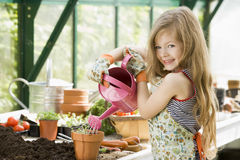 young-girl-watering-plants-greenhouse-4849961